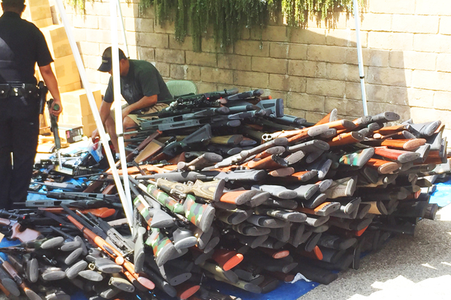 Officers pile weapons, including single bolt-action and semi-automatic rifles, in the alley behind the condo. Photo: Peter Branch