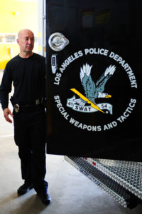 Officer Mullins stands outside of the truck used as SWAT command post. Rich Schmitt/Staff Photographer